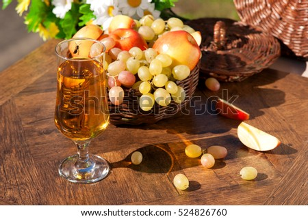 Juice and fruit under the sun. Grapes and apples are in a wicker dish. Apple and grape juice in the glass looks appetizing. Wasp sitting on a glass of juice. Wasp tries to drink flavored juice.
