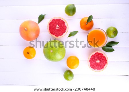 Juice and many citrus on table close-up - stock photo