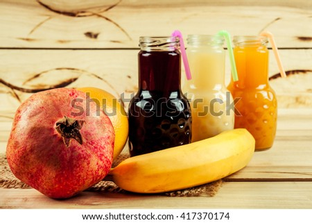 Juice bottle on a wooden background with fruits - stock photo