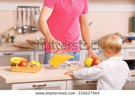 Juice for kids. Loving dad helps his kid with pouring fresh juice into the glass. - stock photo