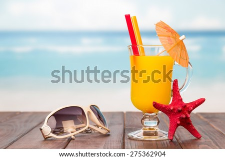 Juice in a glass decorated with umbrella and sunglasses on a wooden table on blured seascape background - stock photo