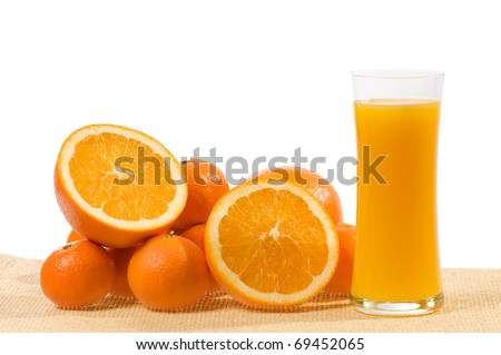 Juice of fresh mixed orange and mandarin fruits in glass and cut and whole fruits lying on beige mat on white background. Horizontal orientation, nobody in frame, studio shot.