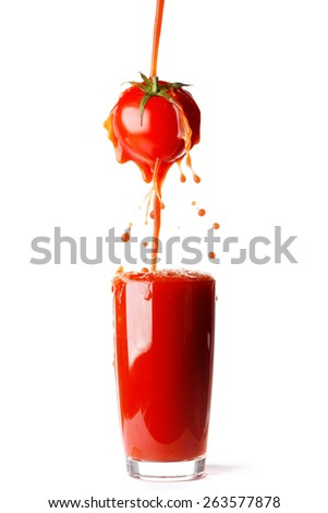 Juice pouring from tomato into glass isolated on white background - stock photo