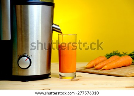 Juicer and carrot juice in glass on yellow background - stock photo