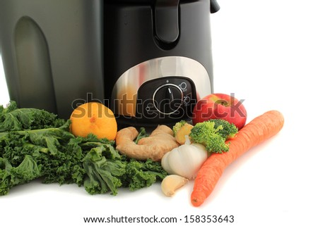 Juicer surrounded by healthy vegetables like carrots, ginger, and kale, ready to make juice