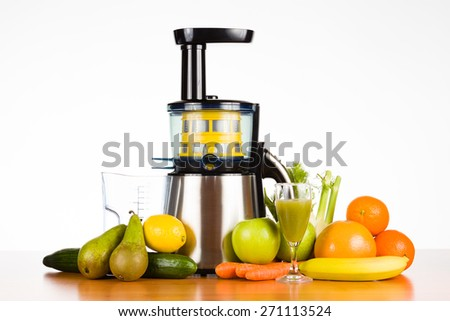 juicer with fruit, vegetables and a glass of juice on wooden table with white background, for a healthy lifestyle - stock photo