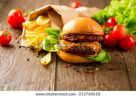 Juicy and fragrant hamburger with fried potatoes on rustic wooden surface. Cheeseburger with tasty buns and juicy meet cutlet with fresh vegetables served with French Fries on a dark wooden table.  - stock photo