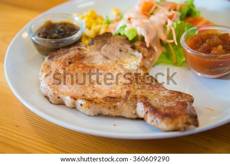 Juicy and tasty grilled pork steak with pepper sauce - stock photo