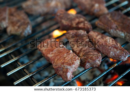 Juicy appetizing steaks from marbled veal are roasted on the grill of a large grill