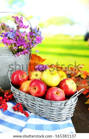 Juicy apples in basket on table on natural background