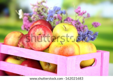 Juicy apples in box on natural background