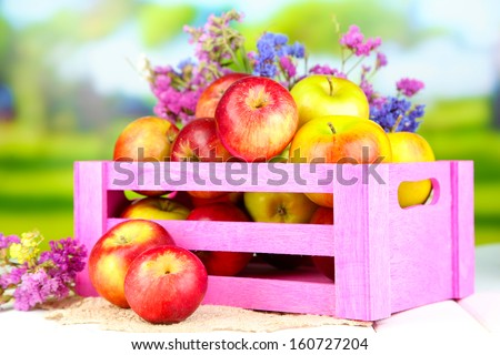 Juicy apples in box on white wooden table on natural background