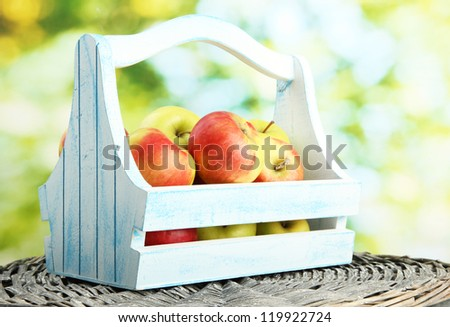 juicy apples in wooden basket, on green background - stock photo