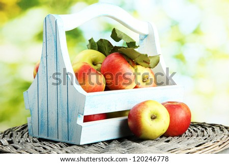 juicy apples with leaves in wooden basket, on green background - stock photo
