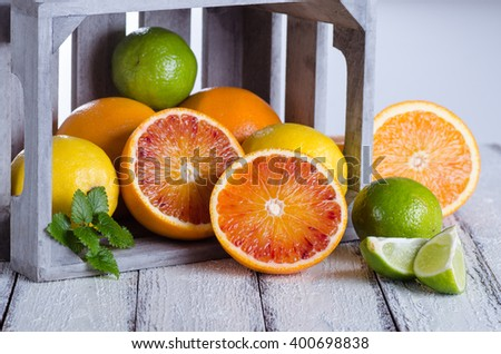 Juicy assorttment of citrus fruits on white wooden background