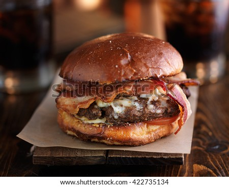 juicy bacon cheeseburger on rustic table - stock photo