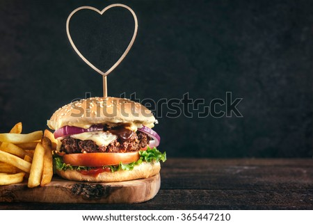 Juicy beef burger and french fries on wooden board with blank space,selective focus - stock photo