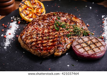 Juicy Beef rump steak from marble beef medium rare with spices, lemon and onion on black stone plate, close-up. Selective focus. - stock photo