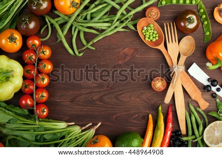 Juicy bright summer vegetable background. Multicolored tomatoes, peppers, young peas, green beans, spinach and other vegetables and herbs on a brown wooden background. Space for text. Vegan concept