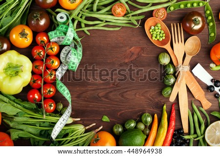 Juicy bright summer vegetable background. Multicolored tomatoes, peppers, young peas, green beans, spinach and other vegetables and herbs on a brown wooden background. Space for text. Vegan concept - stock photo