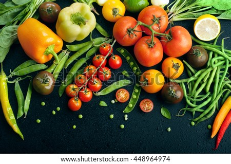 Juicy bright summer vegetable background. Multicolored tomatoes, peppers, young peas, green beans, spinach and other vegetables and herbs on a black background. Space for text. Vegan concept - stock photo
