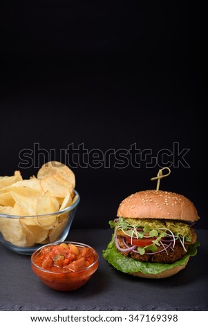 Juicy burger with salty potato chips with ketchup on slate board over black background. Copy space. - stock photo