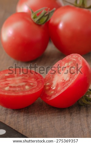 Juicy Cherry tomatoes on wooden background closeup