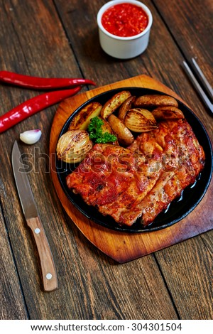 Juicy delicious meat cooked on the grill with vegetables decorated with greenery - stock photo