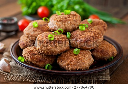 Juicy delicious meat cutlets on a wooden table in a rustic style. Selective focus - stock photo
