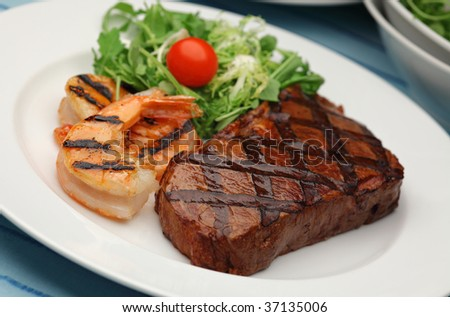 Juicy delicious sirloin steak with grilled shrimps - Surf and Turf - stock photo