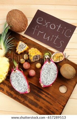 Juicy exotic fruits on wooden cutting board with card