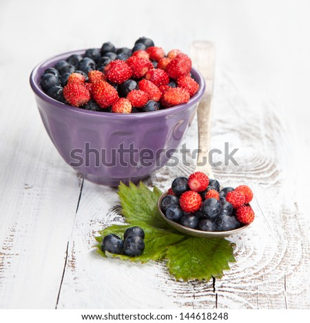 Juicy fresh blueberries and strawberries on a white wooden background