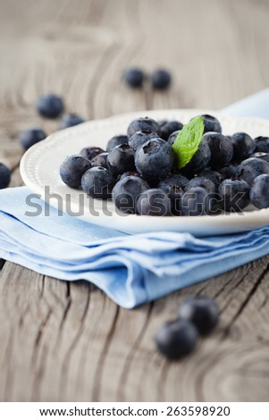 Juicy fresh blueberries in a white plate on old wooden background, selective focus - stock photo