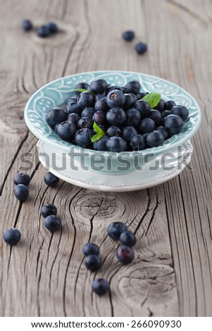Juicy fresh blueberries in a white plate on old wooden background, selective focus