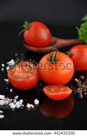 Juicy fresh cherry tomato with salt and black pepper - stock photo