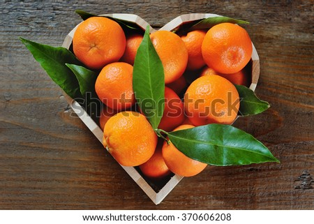 juicy fresh clementines in a heart shaped box on a wooden background - stock photo