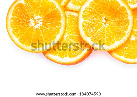 Juicy fresh colorful orange slices piled on top of one another in a vivid border on a white background with copyspace - stock photo