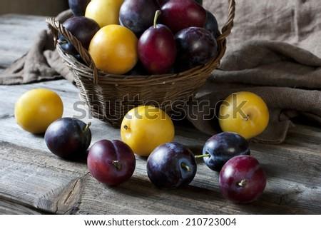 Juicy fresh plums on dark wooden background - stock photo