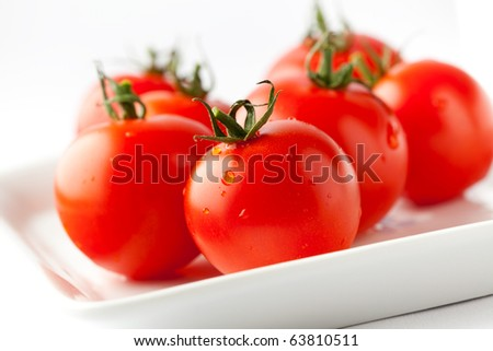 Juicy, fresh red tomatoes on a white plate - stock photo