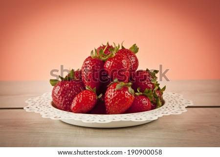 Juicy fresh ripe red strawberries on white plate - stock photo