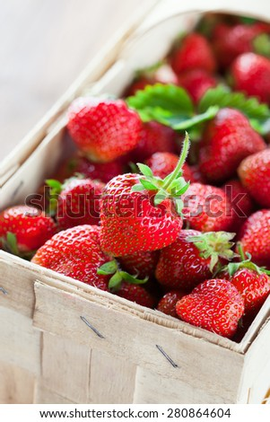Juicy fresh strawberries in a basket on a rustic wooden background, selective focus - stock photo