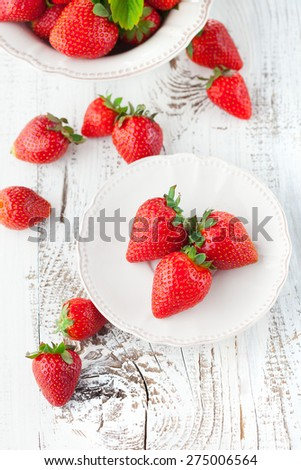 Juicy fresh strawberries in a bowl on a white wooden background, selective focus - stock photo