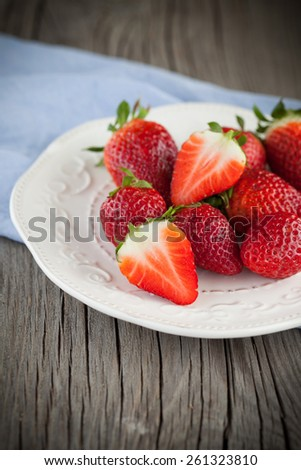 Juicy fresh strawberries in a white bowl on a table, selective focus - stock photo