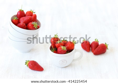 Juicy fresh strawberries in different bowls on white wooden textured background, selective focus
