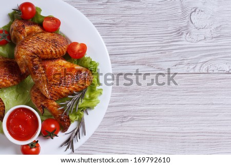 Juicy fried chicken wings with sauce and vegetables on a white plate on a wooden table. top view - stock photo