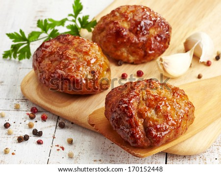juicy fried meat cutlets on wooden cutting board - stock photo