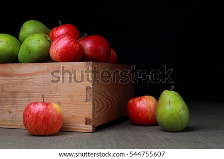 Juicy fruits in old wooden box. Red apples and green pears.