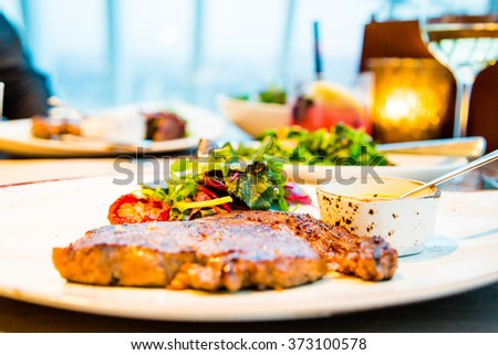 Juicy grilled beef steak on a plate in a restaurant with side salads - stock photo