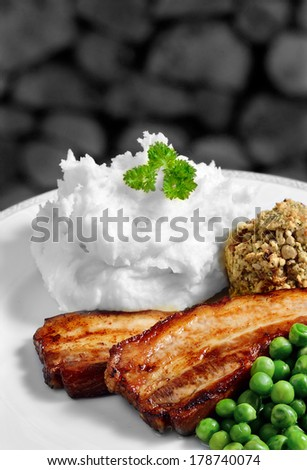 Juicy grilled pork belly strips, creamy mashed potatoes with sage and onion stuffing with garden peas. Perfect pub lunch. From my Pub Food Set. Copy space. - stock photo