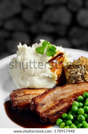 Juicy grilled pork belly strips, creamy mashed potatoes with sage and onion stuffing with garden peas and gravy. Perfect pub lunch. From my Pub Food Set. Copy space. - stock photo